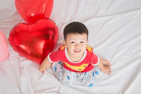 Boy  sibling with balloon  heart shape of love Standard-Bild