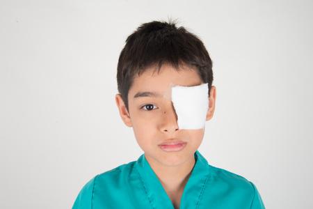 Kleiner Junge hat Augenschmerzen Verwenden Sie einen Verband, um ihn zu bedecken