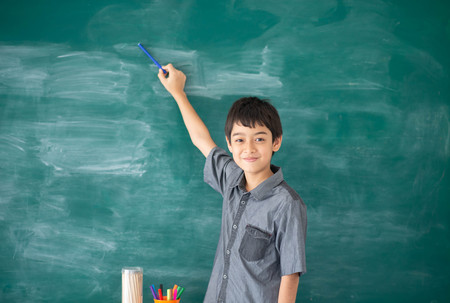 Student boy point to the chalkboard in the classroom Imagens