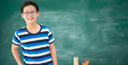 Asian student boy standing in front of chalkboard in the classroom at school Stock Photo