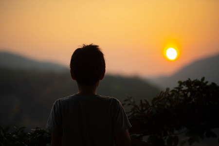 Little boy looking to the sunrise behind the hill in the morning Stock Photo