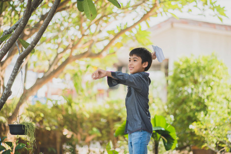 Little boy playing paper rocket in the park Stock Photo
