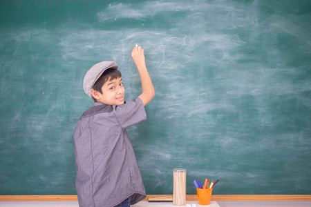 Student boy point to the chalkboard in the classroom Stock Photo