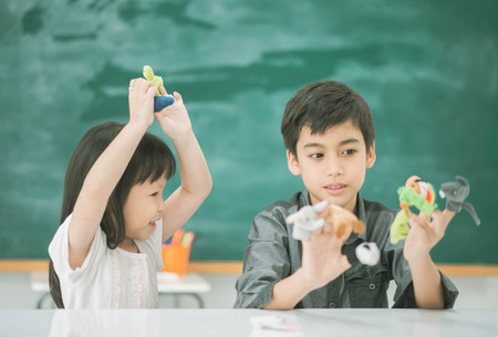 Student boy and girl playing finger doll story telling in the classroom