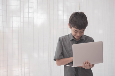 Asian students boy using laptop learning in the classroom at school