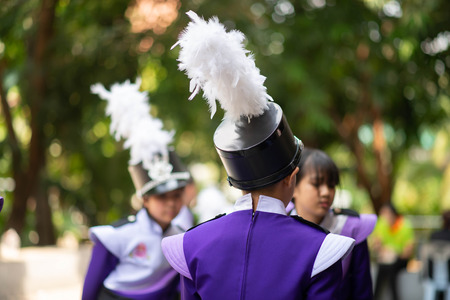 Little boy in purple white uniform play saxophone in  marching band