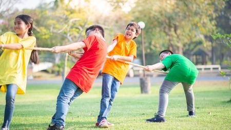 Estudiantes asiáticos niñas y niños juegan tira y afloja