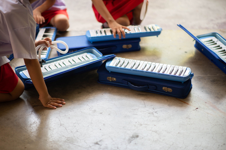 Little student play Melodica Musical Instruments Stock Photo