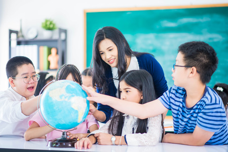 Portrait student looking at globe while listening to teacher with magnifying glass