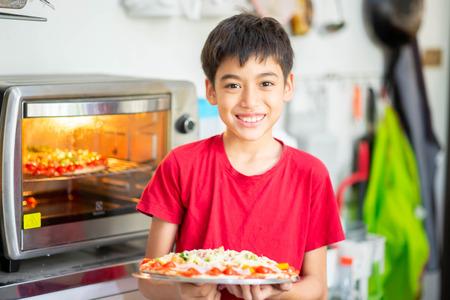 Kleine jongen kookt pizza zelfgemaakt in de keuken thuis