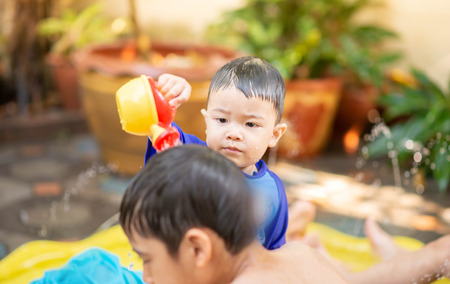 Little Asian boy playing water outdoor house  summer time Stockfoto - 122683056