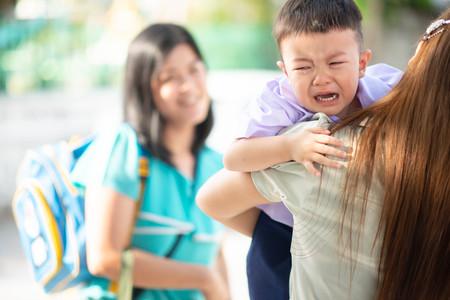 Kleine peuterjongen huilt, eerste dag op school kleuterschool met moeder