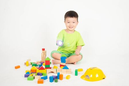 Little Asian toddler boy playing wood blocks wear helmet engineer Zdjęcie Seryjne