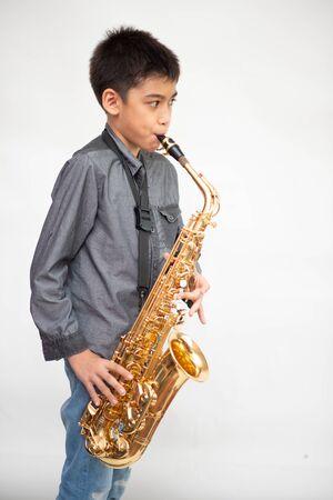 Little asian musician boy playing saxophone instrument 版權商用圖片