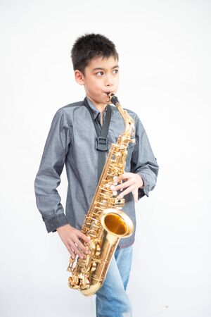 Little asian musician boy playing saxophone instrument 免版税图像