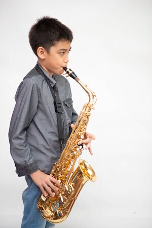 Little asian musician boy playing saxophone instrument Stok Fotoğraf