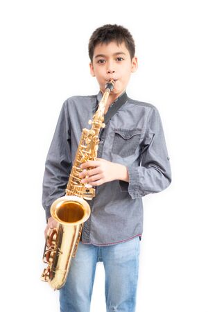 Little asian musician boy playing saxophone instrument 版權商用圖片