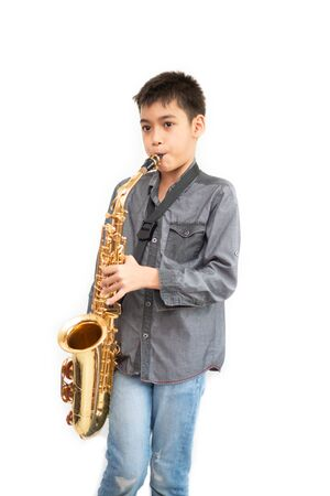 Little asian musician boy playing saxophone instrument