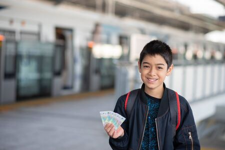 Little boy buying electric ticket and walking in the public sky train station with family