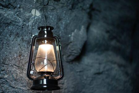 Öllampe hängt an der Höhlensteinwand
