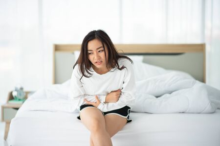Asian woman have stomachache in the morning at bedroom