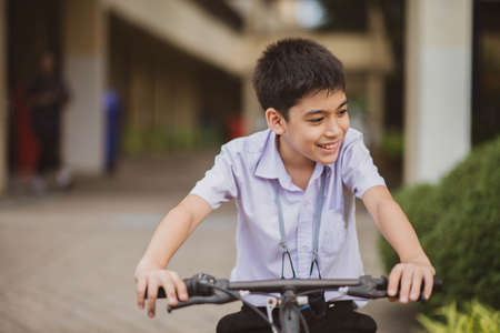 Student boy riding bicycle at school