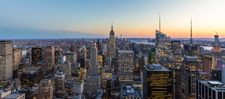 Panoramic photo of New York City Skyline in Manhattan downtown with Empire State Building and skyscrapers at night USA