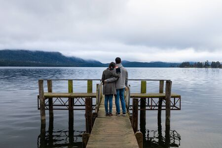 Young Asian couple hugging leaning on shoulder on the bridge Lake Te Anau New Zealand