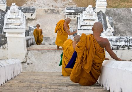 Buddhist monks walking down steep stairs at a temple.