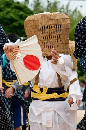 Young boy wearing a full face mask woven from wicker and carrying a paper fan performs in an agricultural festival in Southern Japan. Stock Photo