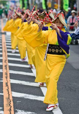 Kagoshima City, Japan, October 26th, 2008. Women in yellow kimono dancing in a symmetrical line during the Taniyama Furusato Matsuri Festival.