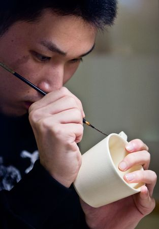 Miyama, Kagoshima, Japan, November 2nd 2008. A Japanese man painting a design onto white Satsuma ware pottery.