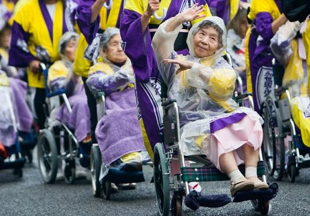 Kagoshima City, Japan, November 3rd, 2008. Elderly Japanese Festival Dancers in wheelchairs at the Ohara Matsuri dance festival. They are being pushed by young volunteers who are also holding umbrellas to ward off the rain. A photo representative of many  Stock Photo - 6887612