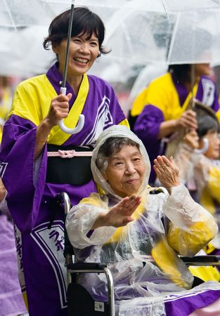 Kagoshima City, Japan, November 3rd, 2008. Elderly Japanese Festival Dancers in wheelchairs brave the rain at the Ohara Matsuri dance festival. They are being pushed by young volunteers who are also holding umbrellas to ward off the rain.