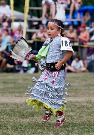 jingling: Ohsweken, Ontario, Canada, July 27, 2008. A young Jingle Dress Dancer performs during the Grand River Champion of Champions Powwow. The metal cones create a jingling sound as the dancer moves.