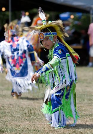 Ohsweken, Ontario, Canada, July 27, 2008. A young grass dancer in green, blue,  and white performs during the Grand River Champion of Champions Powwow.