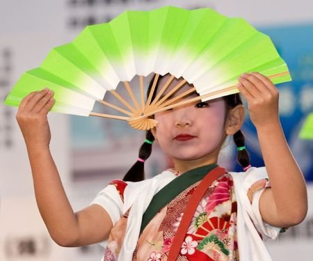 Kagoshima City, Japan, May 3, 2007. A young dancer in costume holding a fan performing onstage in the Daihanya Festival held in Kagoshima City, Japan.
