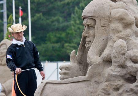 Fukiage, Kagoshima, Japan, April 30, 2007 A sandsculpture artist sprays liquid glue hardener on a sculpture