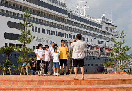 Kagoshima City, Japan, October 8, 2007 A family poses in front of the first cruise ship to dock at the newly built marine port in Kagoshima City, Japan, the  ms Amsterdam  Stock Photo - 6888895