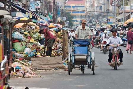 Phnom Penh, Cambodia, January 2, 2008, Cyclo driver peddling past a man working in a garbage receptacle