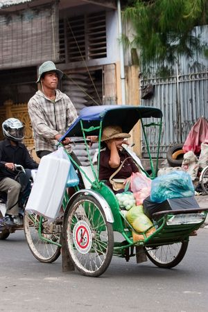 Phnom Penh, Cambodia, January 2, 2008, Cyclo driver peddling his customer and her shopping.