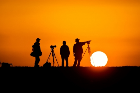 A silhouette of three male photographers talking as the sun sets behind them