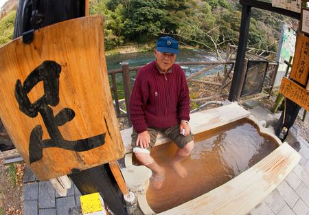Kirishima City, Kagoshima, Japan, January 25, 2009. An elderly Japanese man taking time to relax by soaking his feet at a free outdoor  hotspring
