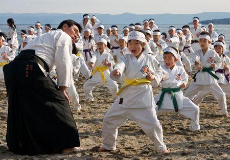 Kagoshima City, Japan, January 13, 2008. Young karate students performing kata on a beach