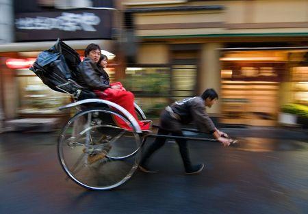 Tokyo, Japan, November 10, 2007 Two people on a rickshaw being pulled on the street in Asakusa, Tokyo, Japan.