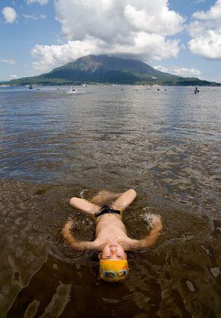 鹿児島市, 日本, 2007 年 7 月 1 日若い男の子、バック グラウンドでアクティブな火山桜島と Iso 浜水に戻ってあります。 報道画像