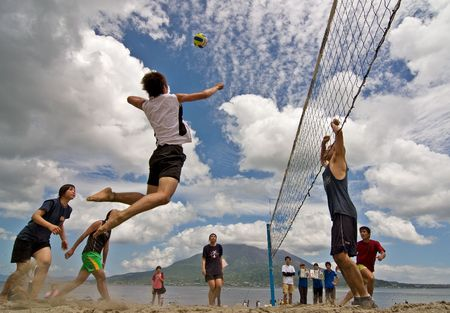 outdoor activities: Kagoshima City, Japan, July 6, 2007. A male volleyball player jumps to spike while another prepares to block during a beach volleyball competition at Iso Beach in Kagoshima City. The active volcano Sakurajima sits in the background.
