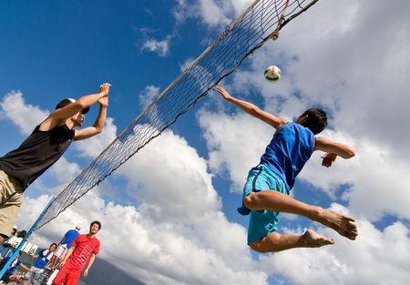 Kagoshima City, Japon, 6 juillet 2007. Un joueur de volleyball saute à pic tandis qu'un autre se prépare à bloquer lors d'une compétition de volleyball de plage à Iso Beach dans la ville de Kagoshima. Banque d'images - 6897537
