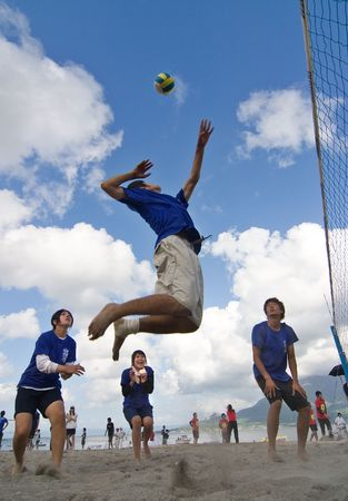 Kagoshima City, Japan, July 6, 2007. A male volleyball player jumps to spike while his teammates look on during a beach volleyball competition at Iso Beach in Kagoshima City.