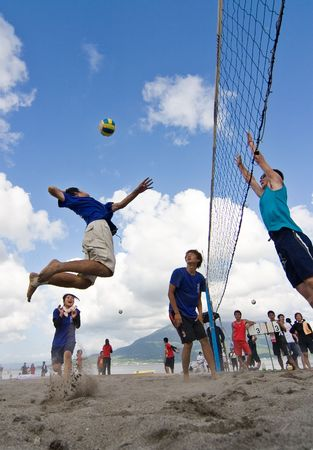 Kagoshima City, Japan, July 6, 2007. A male volleyball player jumps to spike while another prepares to block during a beach volleyball competition at Iso Beach in Kagoshima City. The active volcano Sakurajima sits in the background.